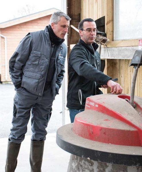 Pierre Rouault et Denis Gourio vérifient la fréquence de passages de l'automate chargé de repousser la ration le long de la table d'alimentation.
