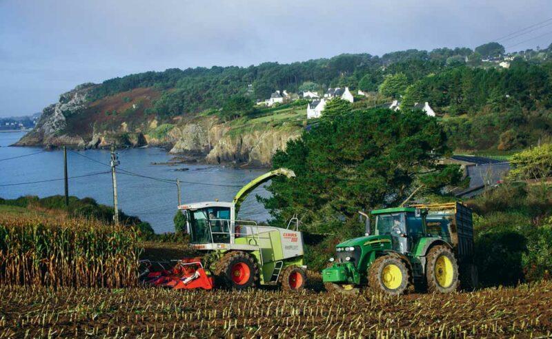 Le photographe apprécie de placer les machines au travail, son sujet principal, dans le paysage côtier breton.