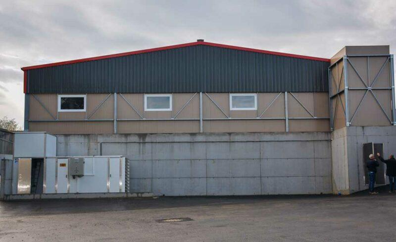 Le bâtiment de 800 m2 est surélevé dans sa partie nord en raison de la configuration du terrain. L'entrée d'air se fait par une gaine dans la partie basse du bâtiment (à gauche), après passage dans le bloc de filtration. Il est ensuite réparti dans la salle par des poteaux de ventilation. L'air vicié est extrait sous les caillebotis et aspiré dans une gaine (à droite). Un espace à cette extrémité pourrait, à l'avenir, accueillir un laveur d'air. Les poteaux de la coque sont en acier remplis sur place de béton.