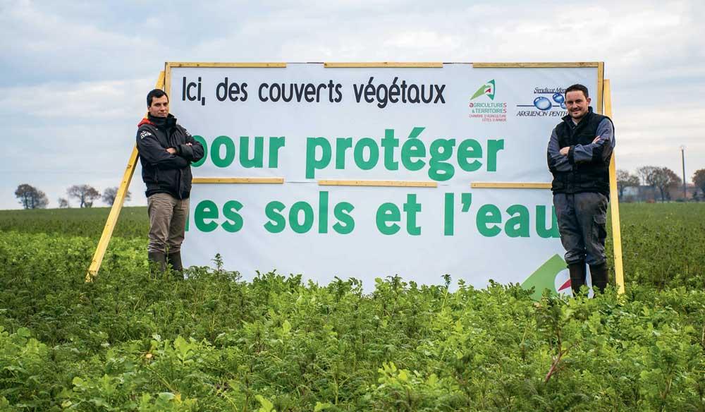 David Bouvier de la Chambre d'agriculture de Dinan et Jérémy Réhel , responsable cultures à la SCEA de la Navette, présentent le panneau de communication placé dans la parcelle d'essais de couverts au bord de la RN 12 à Plénée-Jugon.
