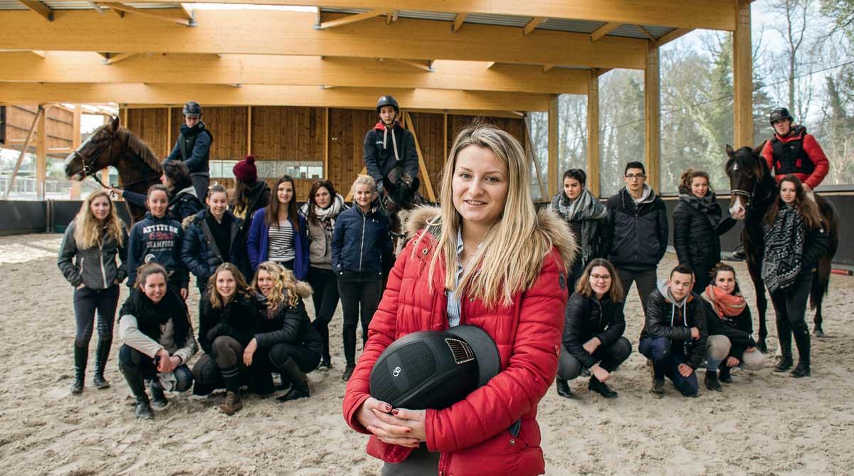 Dans le nouveau manège du lycée de Kernilien, Julie Massey prend la pose avec sa classe de Bac Pro CGEH accompagnée de Stéphane Quéméner, enseignant en techniques équestres.