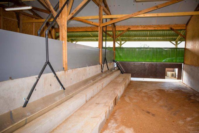 Le bâtiment d'engraissement sur paille (100 kg en moyenne par porc), avec rideaux amovibles et courette extérieure. Les caillebotis sont exclus dans le groupement Bio Direct. Chaque case comprend 33 places de porcs: 1,8 m2 à l'intérieur + 0,5 m2 à l'extérieur par porc. Le bâtiment est en ventilation statique. Les cases de post-sevrage ont une partie bien isolée, avec les nourrisseurs, et une partie ouverte sur l'extérieur.