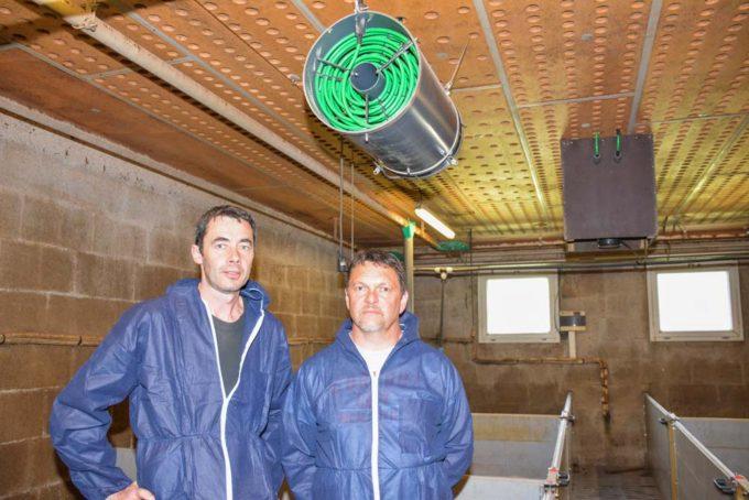 Bruno Hélo (à gauche) et Stéphane Richard, installateur, sous l'un des brasseurs. Chaque salle en possède deux, reliés chacun à l'un des capteurs placé dans les cheminées (au second plan). Un simple lavage à l'eau entre deux bandes suffit pour les nettoyer. Les capteurs, dans les cheminées s'autonettoient en mode chauffage (condensation).