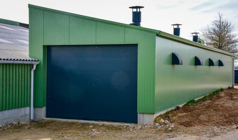 L'air entre par les quatre volets automatisés et sort par les deux cheminées sur le toit (troisième cheminée au-dessus de la laiterie). Le portail, étanche, facilite le nettoyage et l'évacuation des animaux.