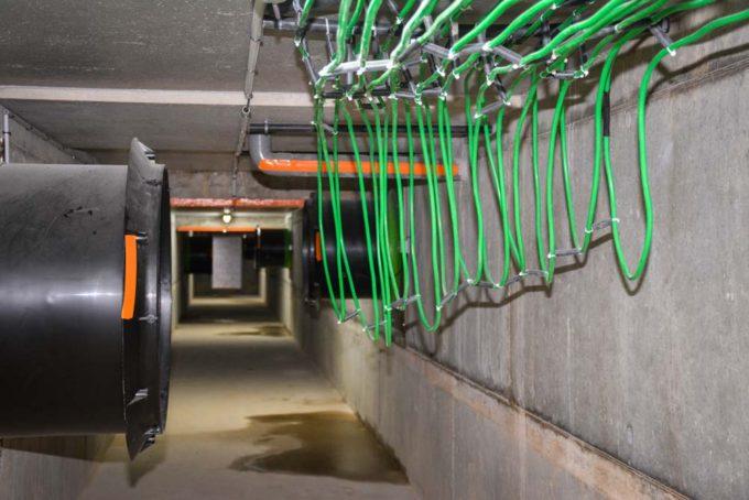 Le bâtiment est équipé d'une gaine centralisée d'extraction de l'air chaud et vicié. Les calories y sont récupérées à l'aide d'un gaz circulant dans un circuit de tuyaux de cuivre plastifié (en vert). Une pompe à chaleur récupère ces calories pour chauffer de l'eau qui circule sous les plaques chauffantes en maternité et dans une unité de soufflage dans les combles (échange eau-air). Cette unité assure un minimum de 12°C de température dans les combles (séparées au-dessus de chaque compartiment du bâtiment) toute l'année.