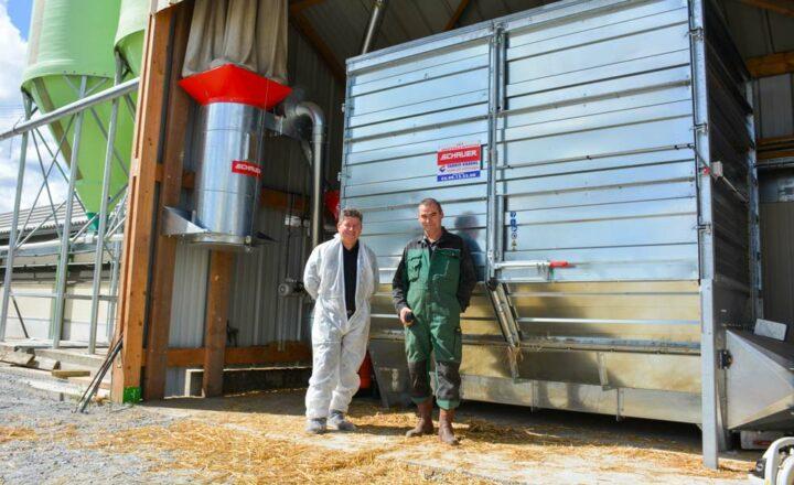 Hervé Tanguy, gérant de Tardif-Vassal et Yoann Duperrin devant la pailleuse en poste fixe de marque Schauer qui alimente en paille broyée les 3 500 m2 de bâtiments en production de canard pré-gavage.