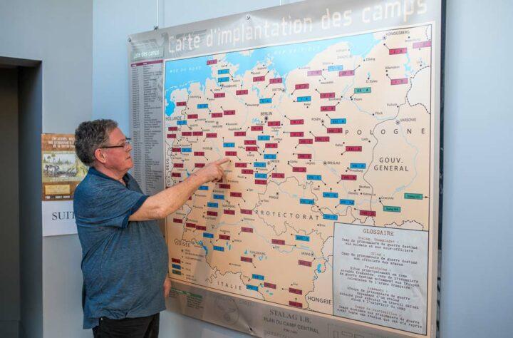 Yannick Le Guennic, membre de l'association qui gère le musée, devant la carte répertoriant les camps en Allemagne et en Pologne où étaient envoyés les prisonniers de guerre français.