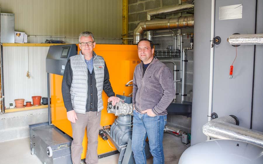 Stéphane Dahirel, aviculteur à Lanouée (56), et Raphaël Lemercier, responsable technique chez GRD thermique, devant la chaudière à biomasse de 130 kW de puissance.