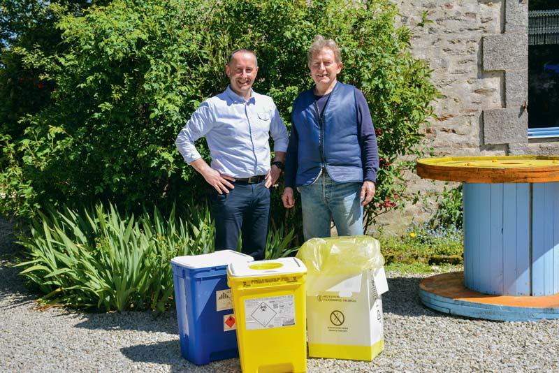 Guy Le Bouter et Bruno Robert, responsable de secteur La Collecte Médicale, présentent les containers de couleur qui correspondent chacun à un type de déchets d'élevage.