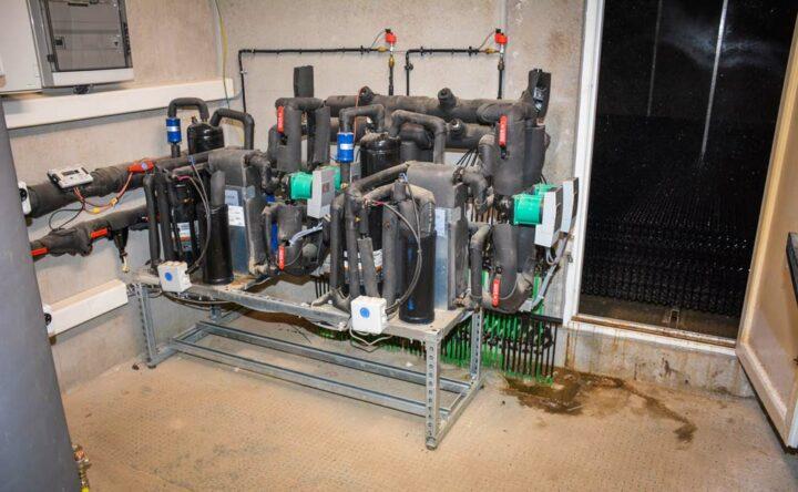 Le local technique. Derrière la porte, les calories sont récupérées sous le laveur d'air par un gaz contenu dans les tuyaux verts. Ces tuyaux présentent des caractéristiques uniques de résistance à l'ammoniac, selon le concepteur.