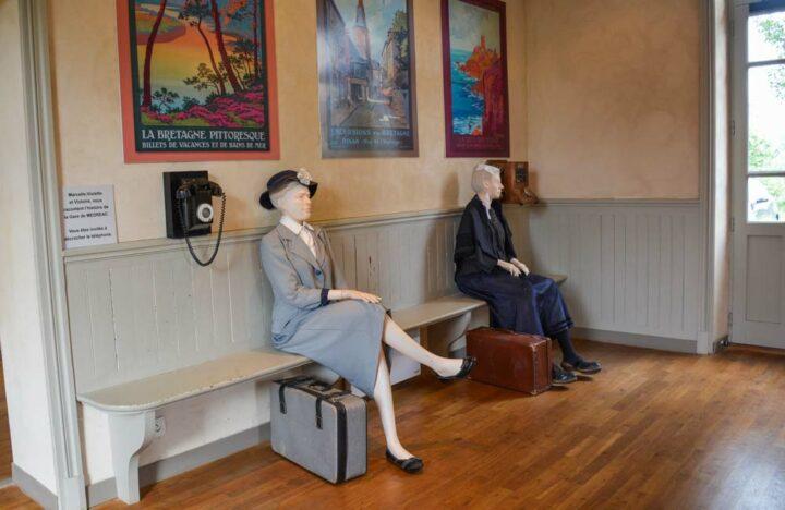 Dans le hall d'accueil, des passagères de différentes époques attendent le train.