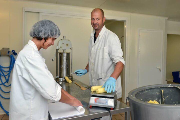 Benoît à la découpe, Isabelle à l'emballage. Le beurre au lait cru se conserve certes moins longtemps mais il garde toutes  les qualités organoleptiques d'un lait de ces vaches exclusivement nourries à l'herbe et au foin séché.