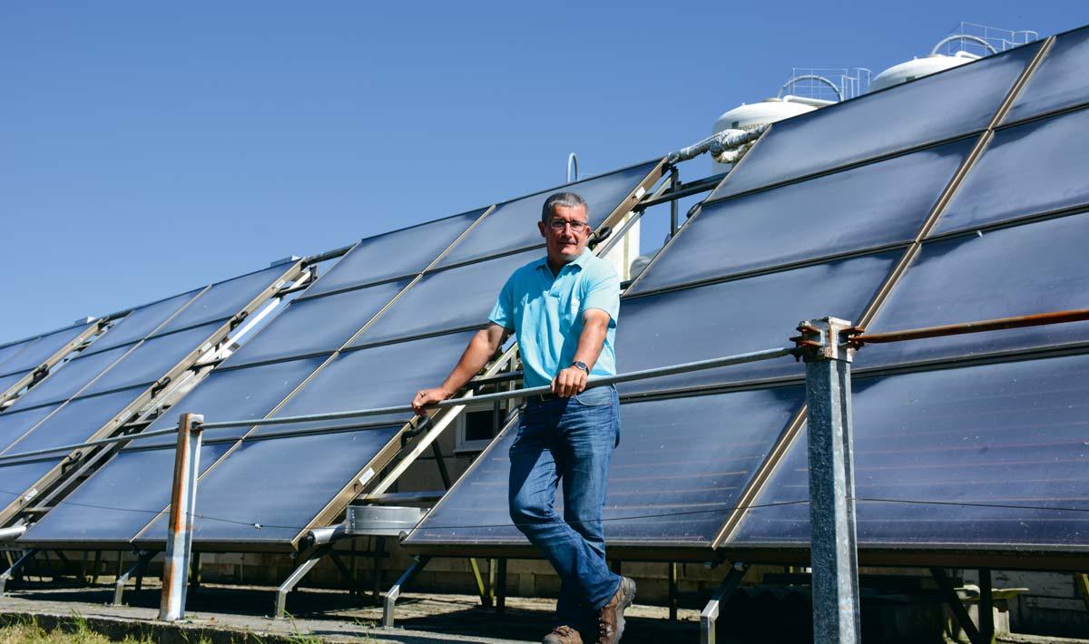 Christian Merret, éleveur de veaux de boucherie à Henvic (29) devant ses panneaux solaires thermiques.