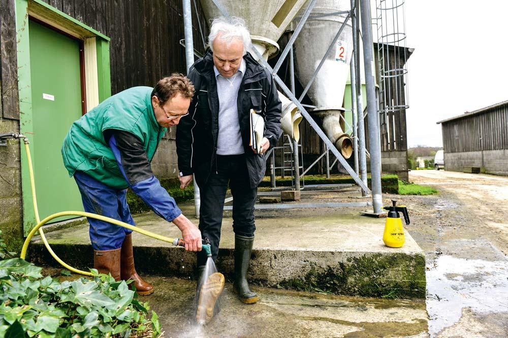 Patrick Robert, éleveur laitier à Bréhand-Moncontour montre à Félix Mahé comment, en les déchaussant à moitié, il est facile de nettoyer le dessous des bottes avant d'entrer dans la stabulation. Qui dit « bio sécurité » n'exclut pas bon sens paysan et pragmatisme !